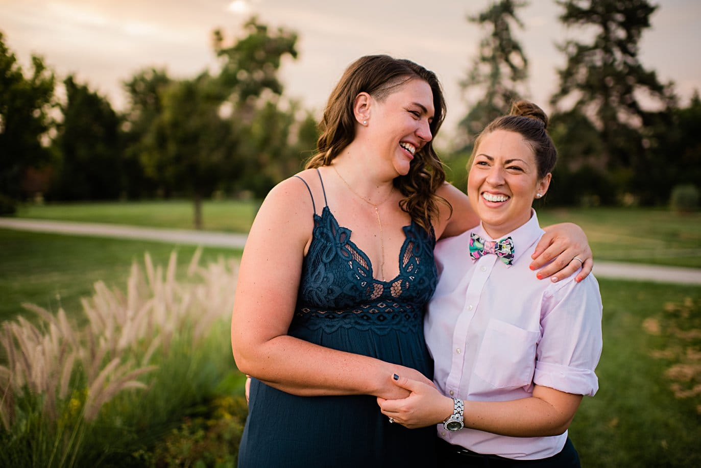 bride in navy summer dress and bride in bow tie get engaged in City Park Denver by Denver proposal photographer Jennie Crate
