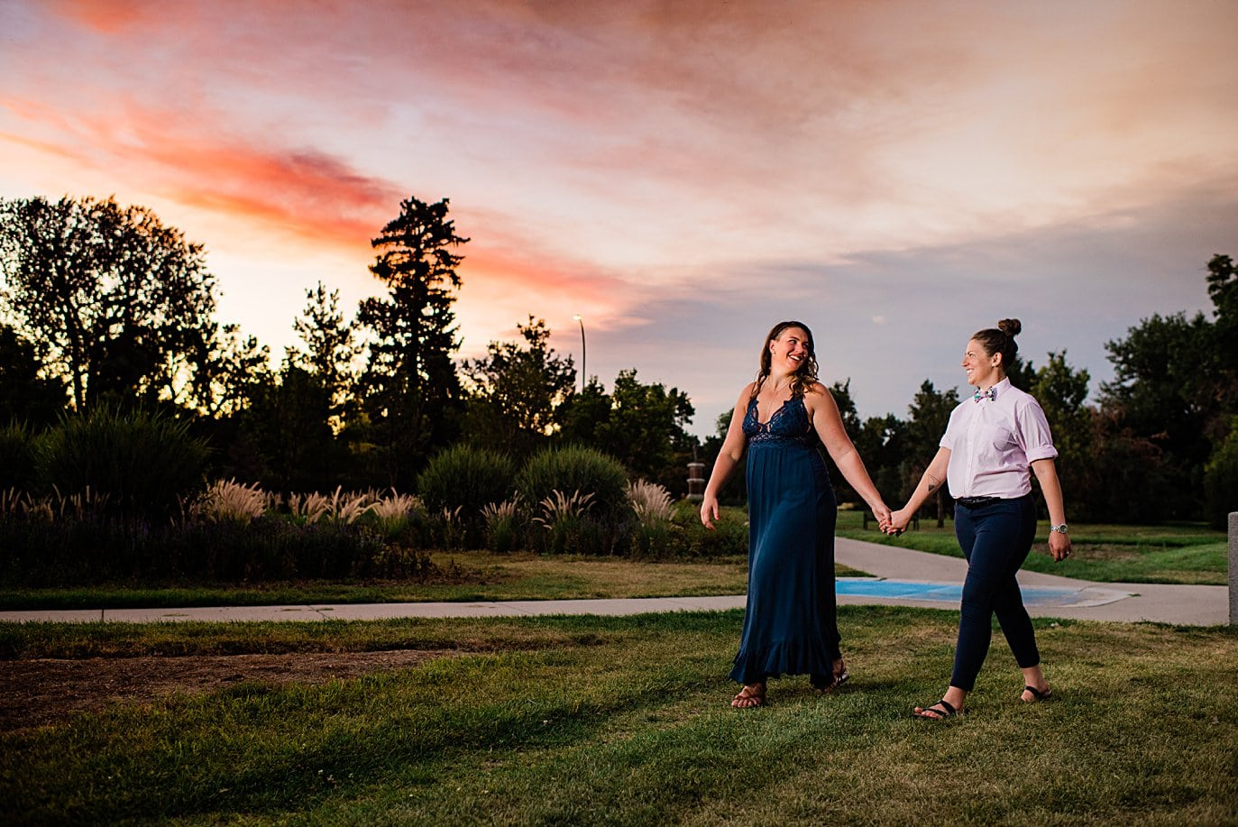 two brides walk hand in hand at sunset after proposal in City Park Denver by Denver proposal photographer Jennie Crate
