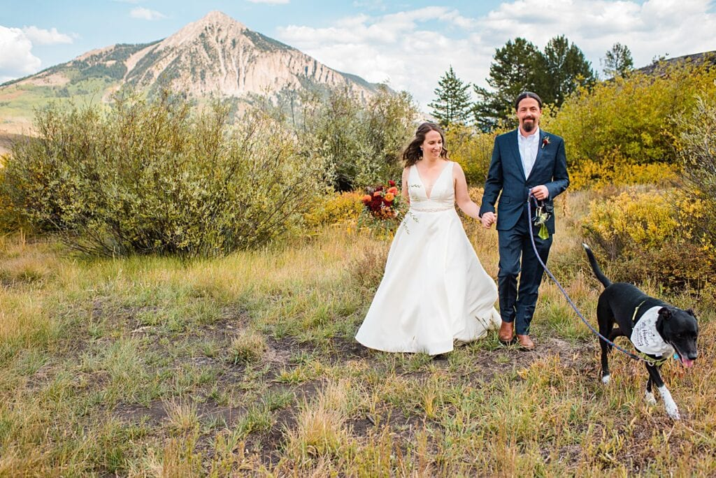 bride and groom walk hand in hand at peanut lake after first look at Crested Butte Elopement by Crested Butte elopement photographer Jennie Crate