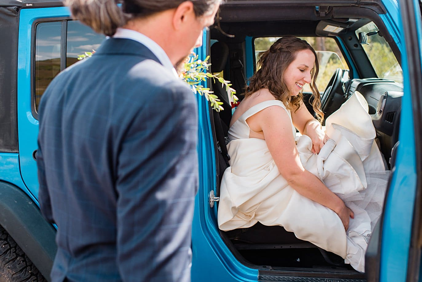 bride gets into blue jeep for drive to ceremony spot in Crested Butte for private elopement by Aspen wedding photographer Jennie Crate