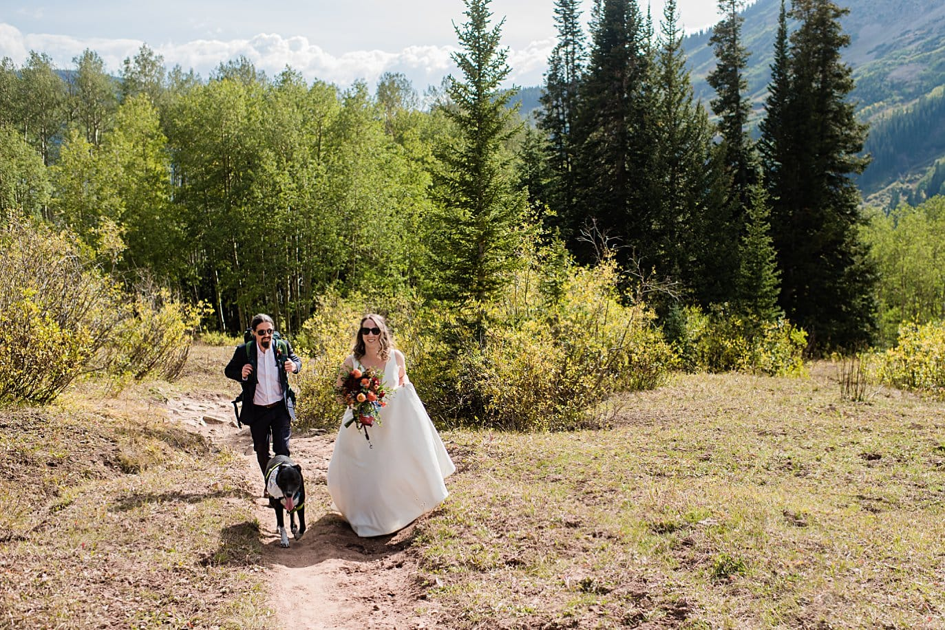 bride and groom hike to ceremony spot in meadow up gothic road in Crested Butte for private elopement by Aspen wedding photographer Jennie Crate