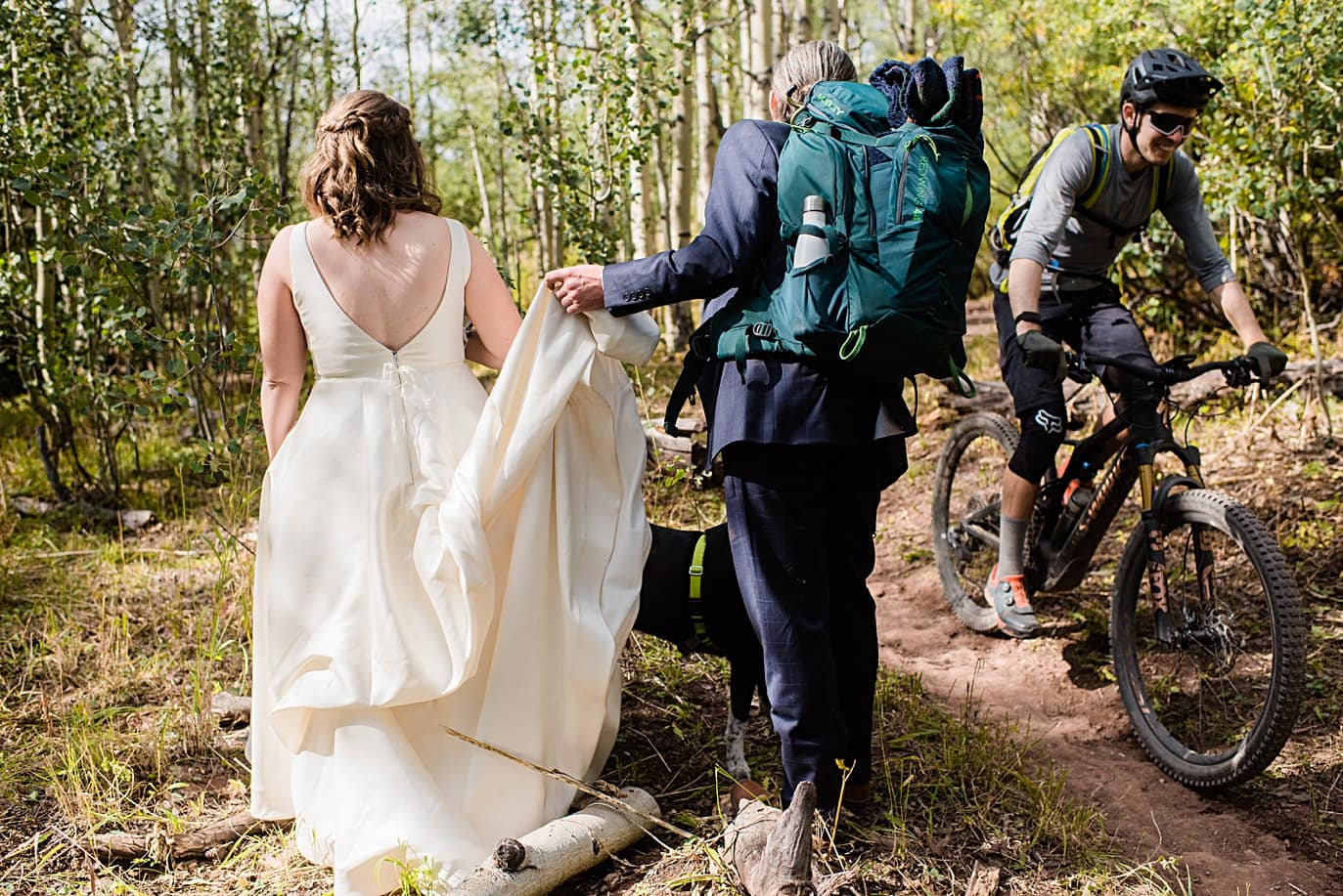 bride and groom hike past mountain biker on way to ceremony spot in Crested Butte for private elopement by Aspen wedding photographer Jennie Crate