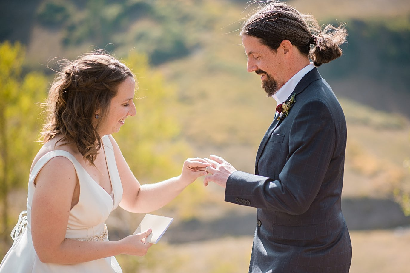 bride puts ring on groom's finger during intimate ceremony in Colorado by Colorado wedding photographer Jennie Crate