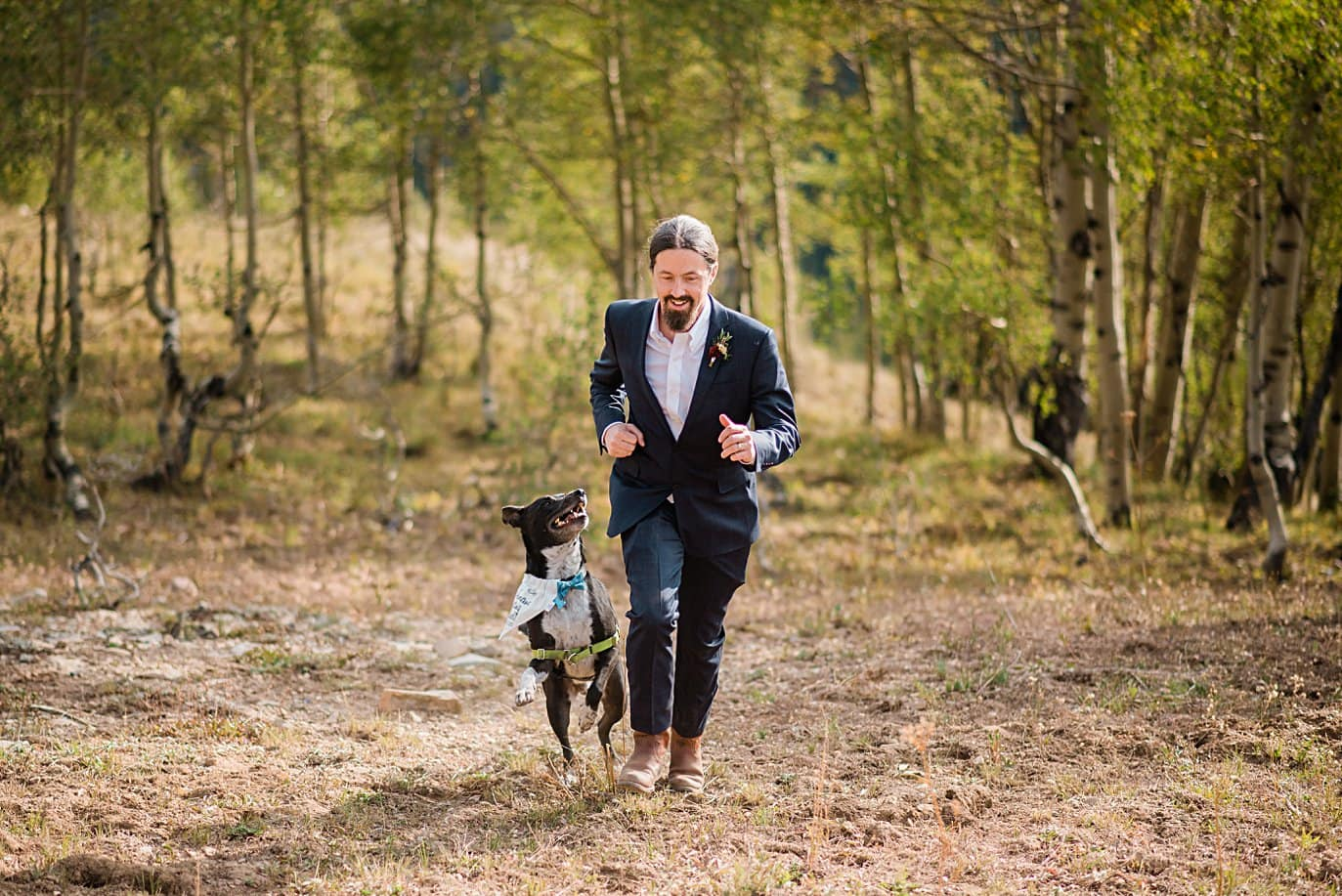 groom runs with dog on wedding day in meadow in Colorado mountain by Denver wedding photographer Jennie Crate