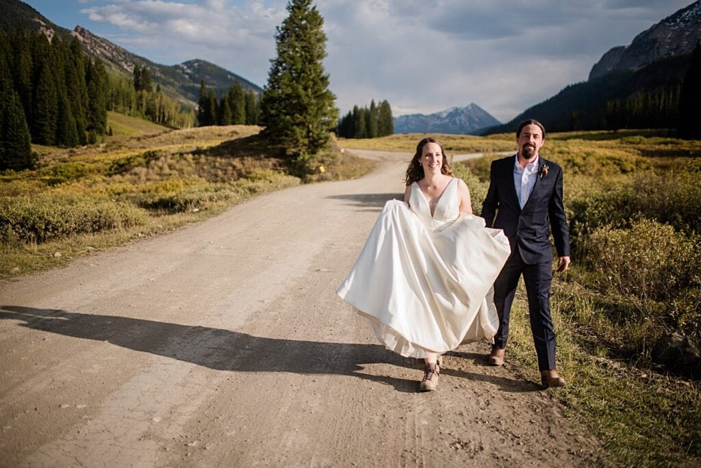 bride and groom walk down road on Gothic Pass at Crested Butte elopement by Denver wedding photographer Jennie Crate