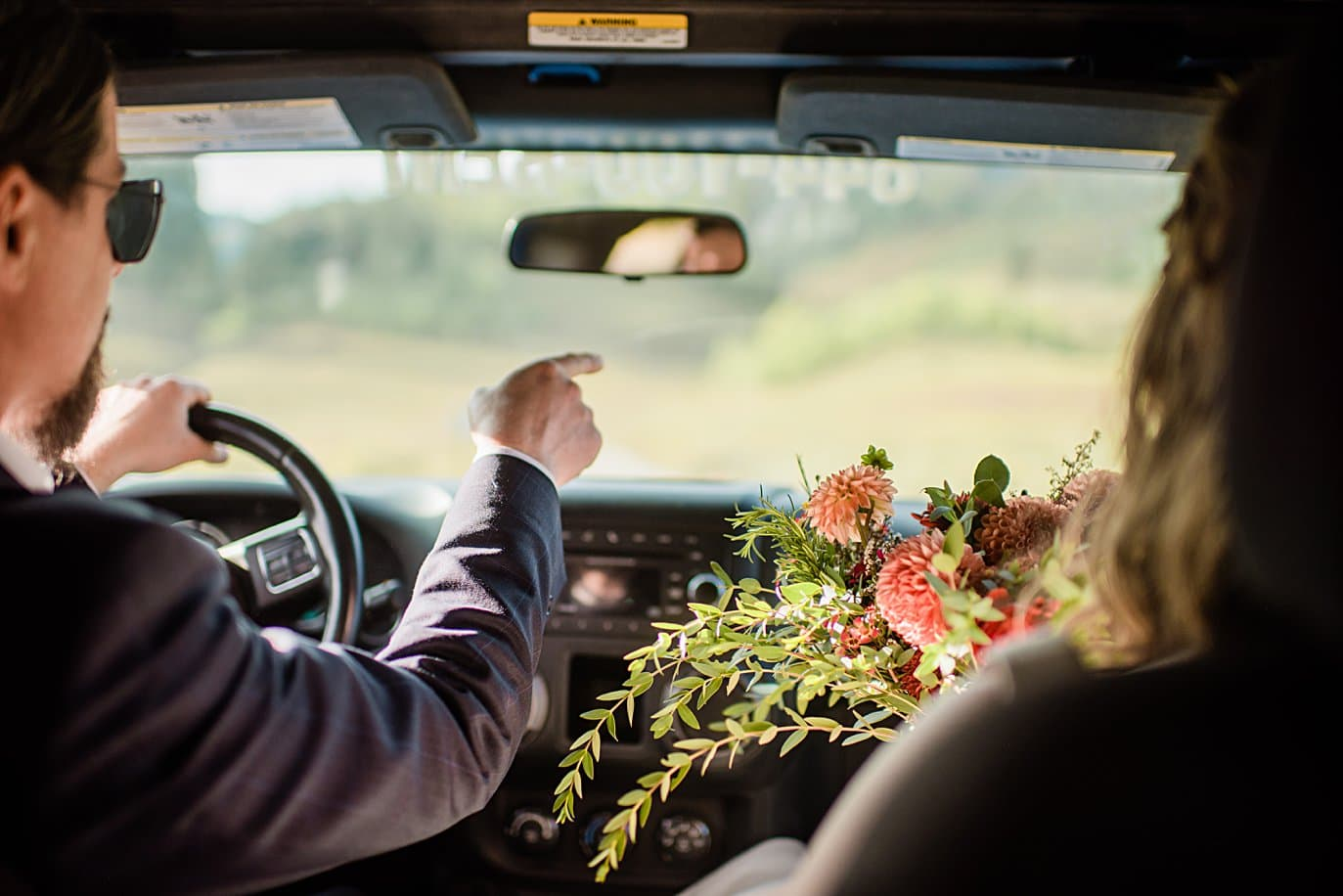 bride and groom drive to lake for photos at Crested Butte elopement by Denver wedding photographer Jennie Crate