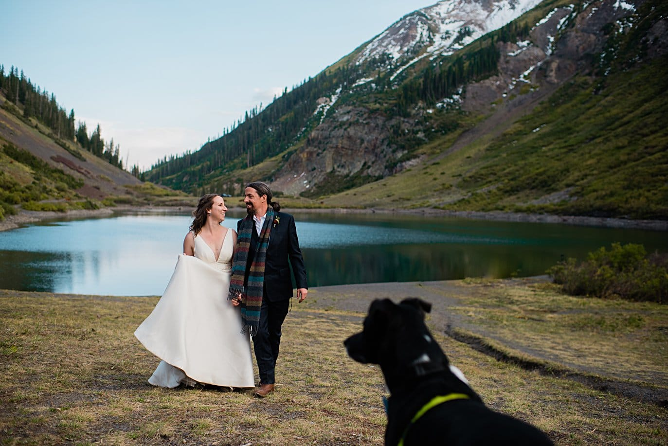 bride and groom walk by lake with dog looking on at Crested Butte elopement by Denver wedding photographer Jennie Crate