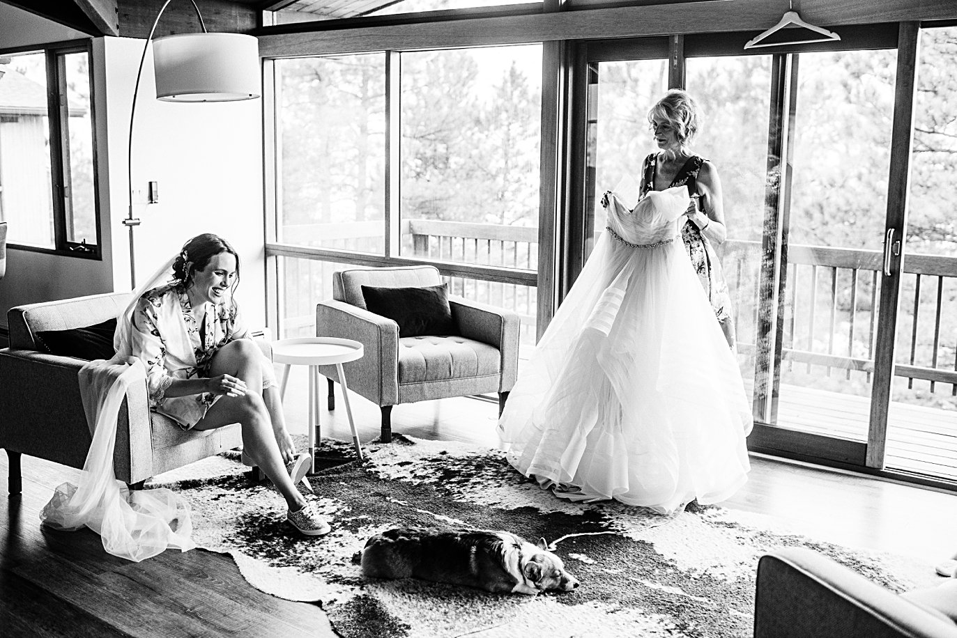 bride puts on shoes before putting on wedding dress with dog in living room at Colorado wedding by boulder wedding photographer Jennie Crate