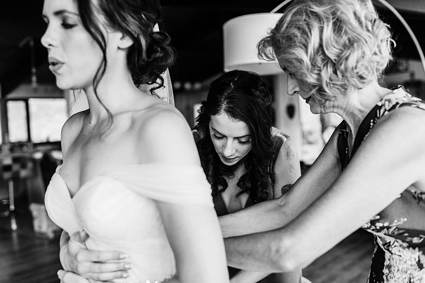 bride takes a deep breath as mom zips up wedding dress at Colorado wedding by boulder wedding photographer Jennie Crate