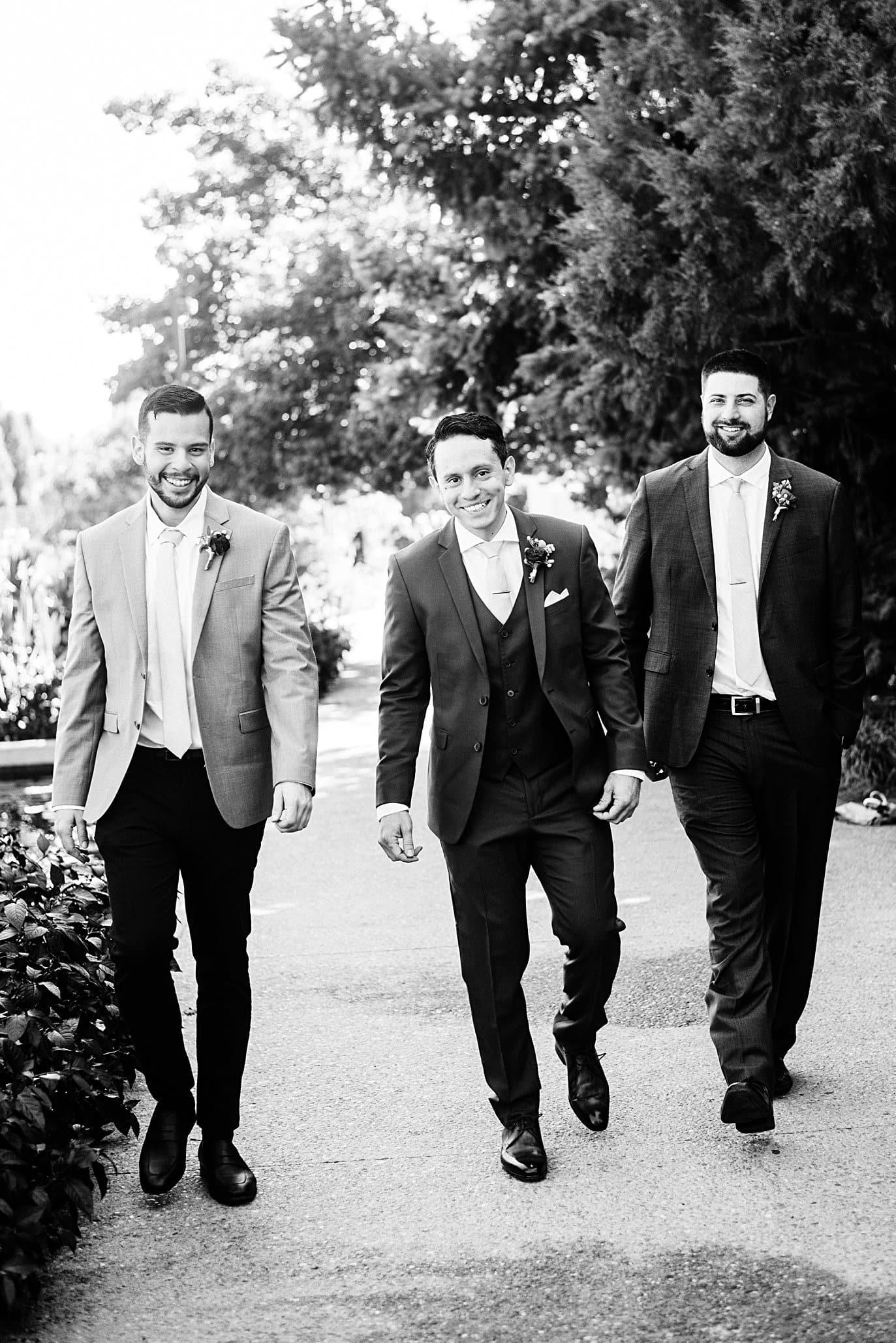 groom and groomsmen walk around gardens before ceremony at Denver Botanic Gardens wedding by Denver wedding photographer Jennie Crate