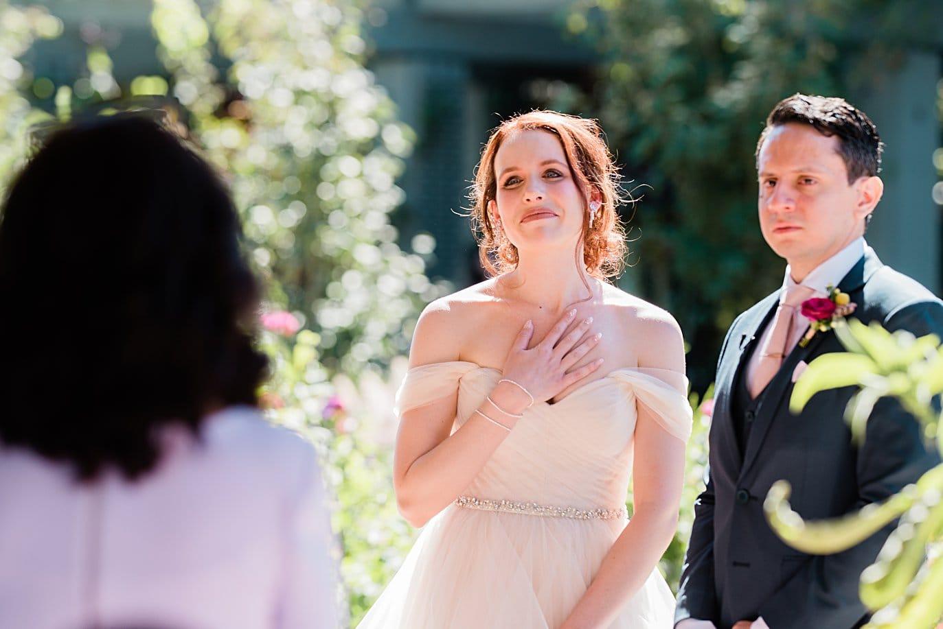 bride gets emotional during mother of groom speech at wedding ceremony at Denver Botanic Gardens microwedding by Denver wedding photographer Jennie Crate