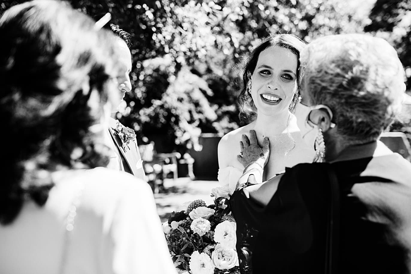 bride and groom embrace family after ceremony at Denver Botanic Gardens microwedding by Boulder wedding photographer Jennie Crate