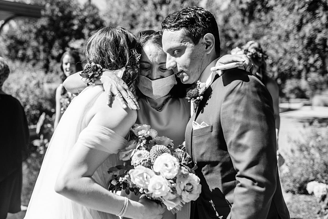 groom's mom hugs couple after ceremony at Denver Botanic Gardens microwedding by Boulder wedding photographer Jennie Crate