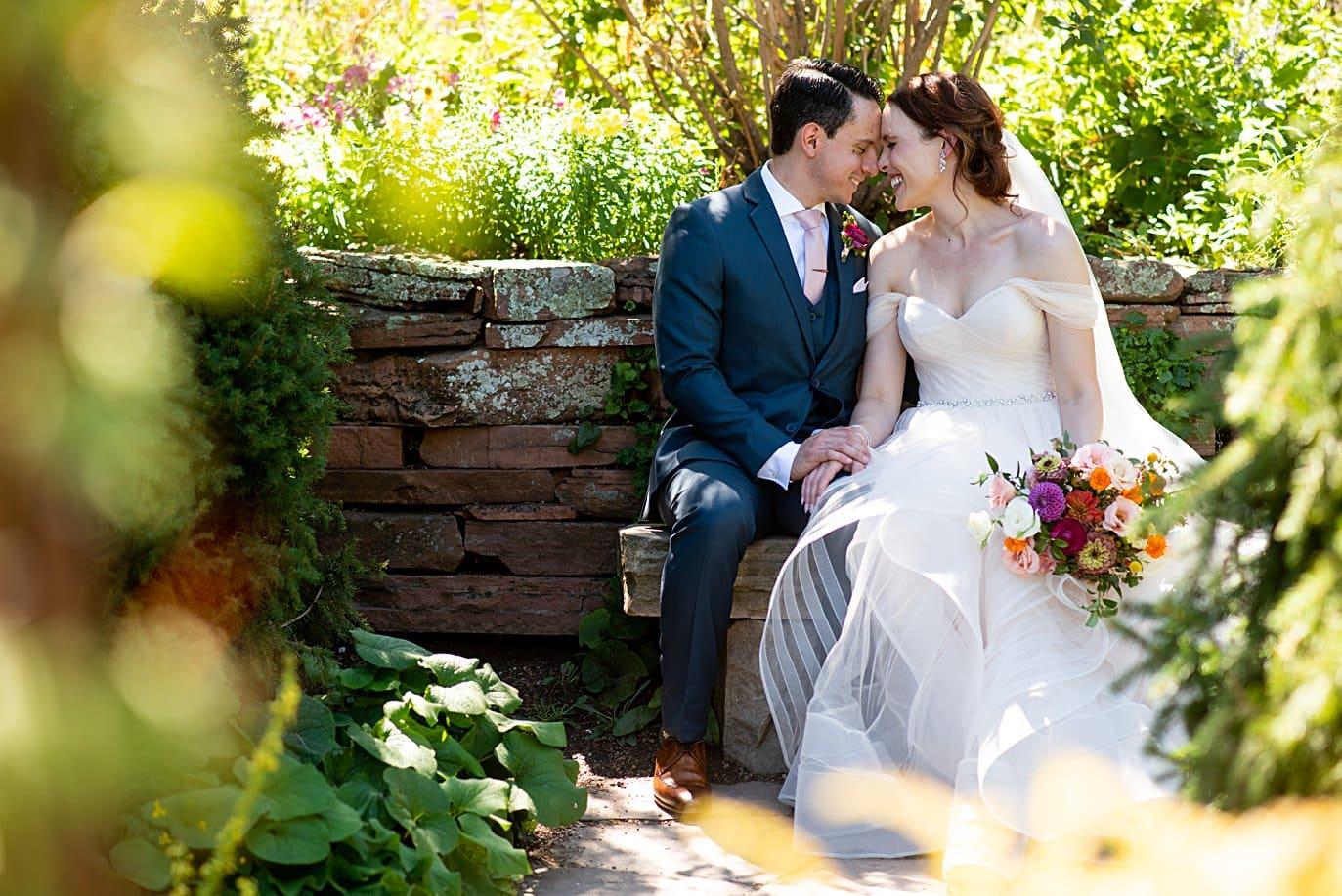 bride and groom find hidden stone bench at Denver Botanic Gardens microwedding by Boulder wedding photographer Jennie Crate