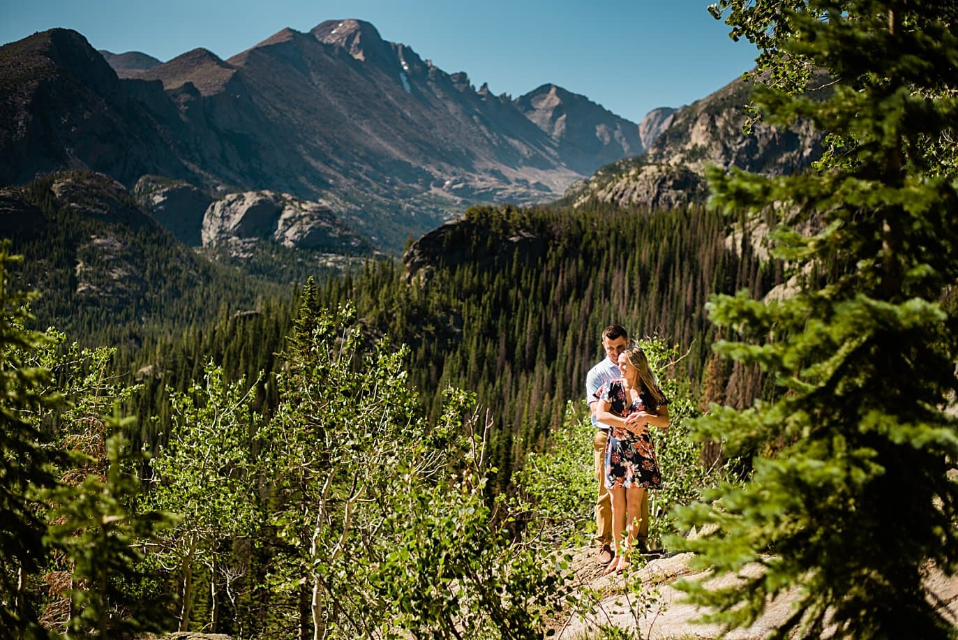 engaged couple hiking to dream lake engagement by Denver wedding photographer Jennie Crate