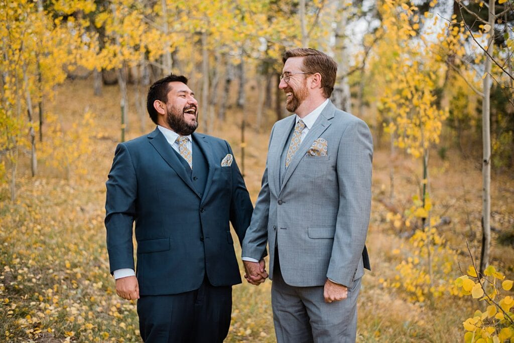two grooms in navy and gray suits laugh in fall aspen trees in Golden Gate Canyon by Colorado gay wedding photographer Jennie Crate
