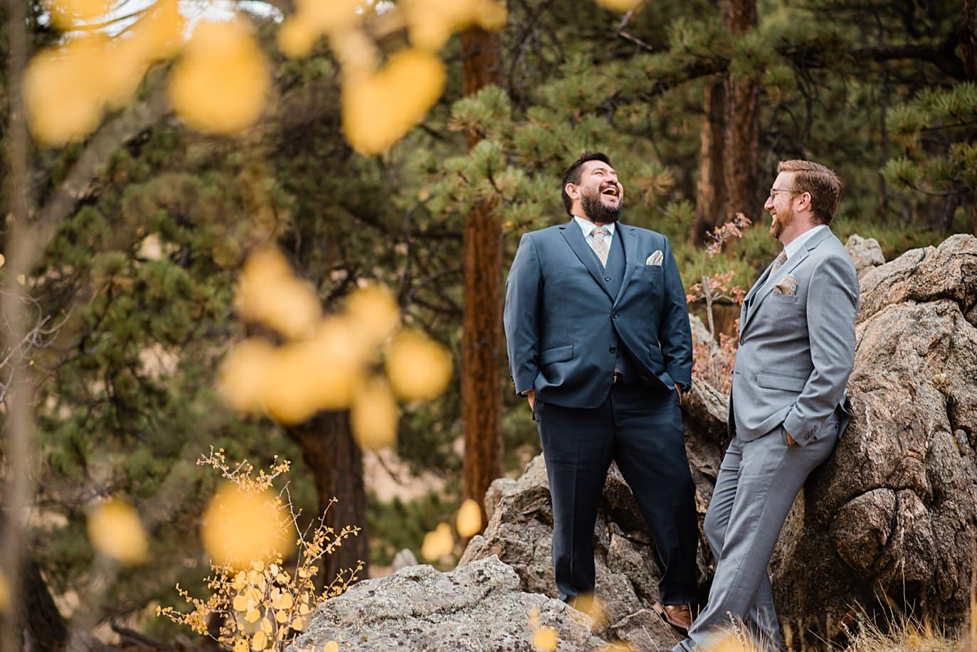 grooms laugh on rocks in Golden Gate Canyon by Colorado gay wedding photographer Jennie Crate