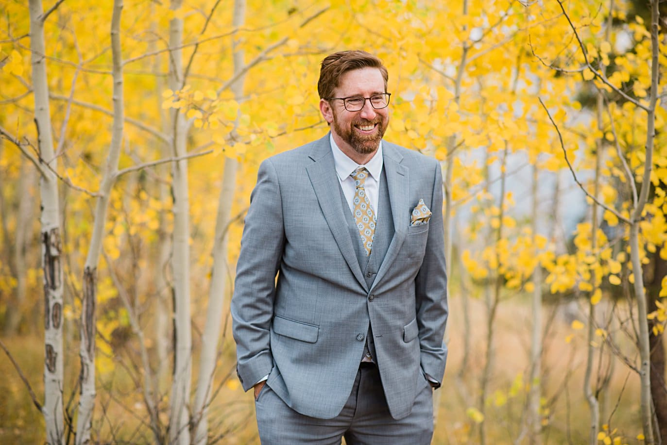 room in grey suit flanked by yellow aspens in fall in Golden Gate Canyon by Colorado gay wedding photographer Jennie Crate