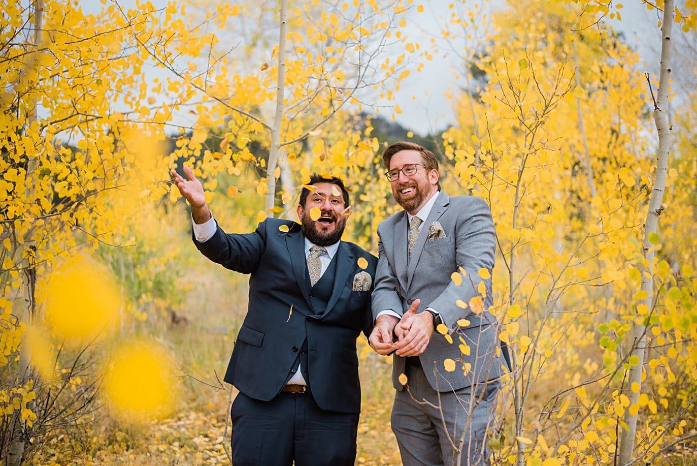 grooms throw leaves in Golden Gate Canyon by Colorado gay wedding photographer Jennie Crate