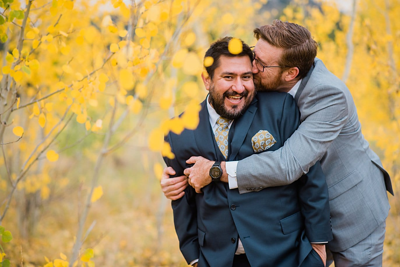 grooms cuddle during engagement session in Golden Gate Canyon by Colorado gay wedding photographer Jennie Crate