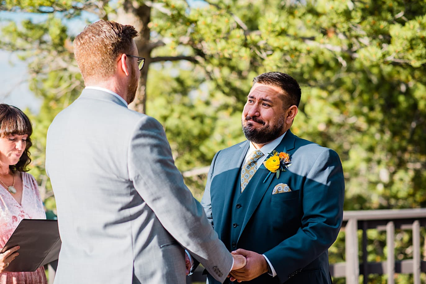grooms say vows at Panorama point during LGBTQ wedding by Colorado LGBT photographer Jennie Crate