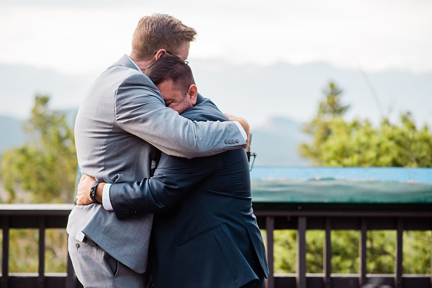 grooms hug after ceremony at Panorama point during LGBTQ wedding by Colorado LGBT photographer Jennie Crate