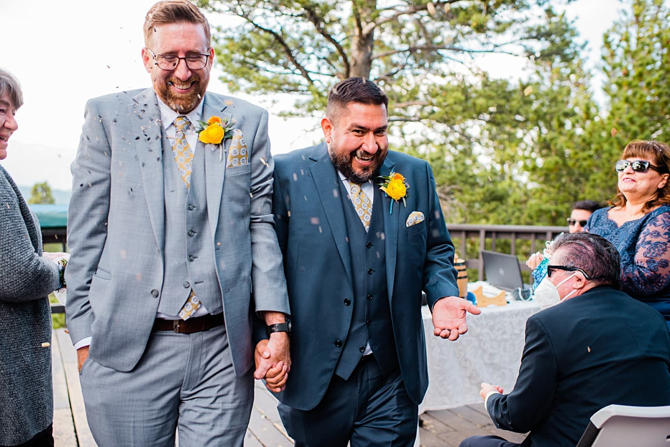 grooms walk down aisle to shower of birdseed at Panorama point during LGBTQ wedding by Colorado LGBT photographer Jennie Crate