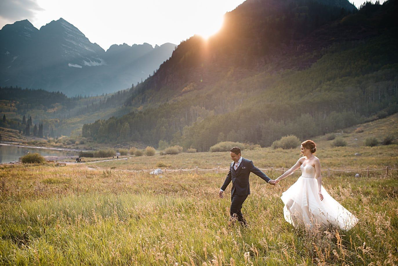 bride and groom walk hand in hand in front of Maroon Bells peaks at sunset at fall Maroon Bells wedding by Aspen wedding photographer Jennie Crate