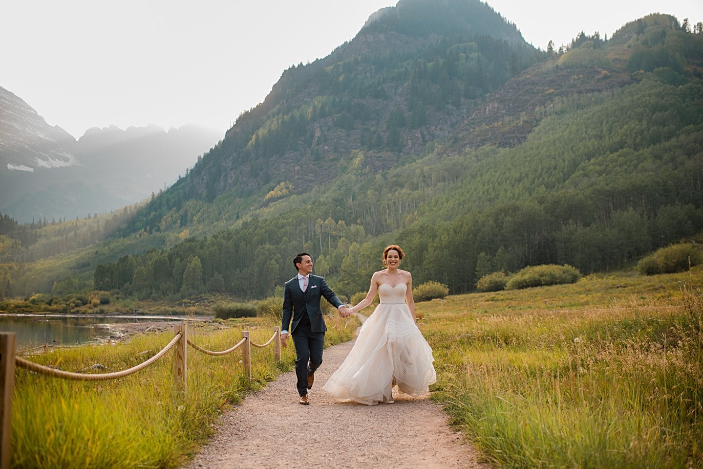 bride and groom walk along path at fall Maroon Bells wedding by Aspen wedding photographer Jennie Crate