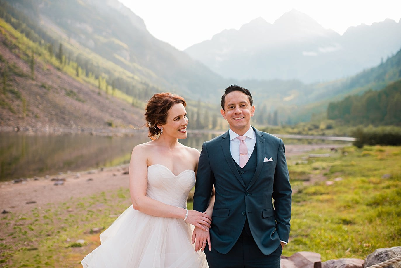 bride and groom in front of Maroon Lake at fall Maroon Bells wedding by Aspen wedding photographer Jennie Crate