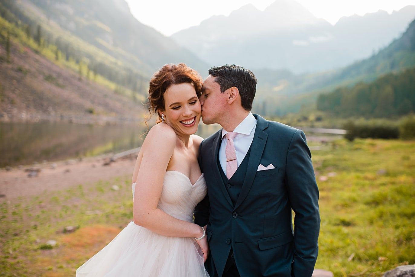 bride and groom cuddle in front of Maroon Lake at fall Maroon Bells wedding by Aspen wedding photographer Jennie Crate
