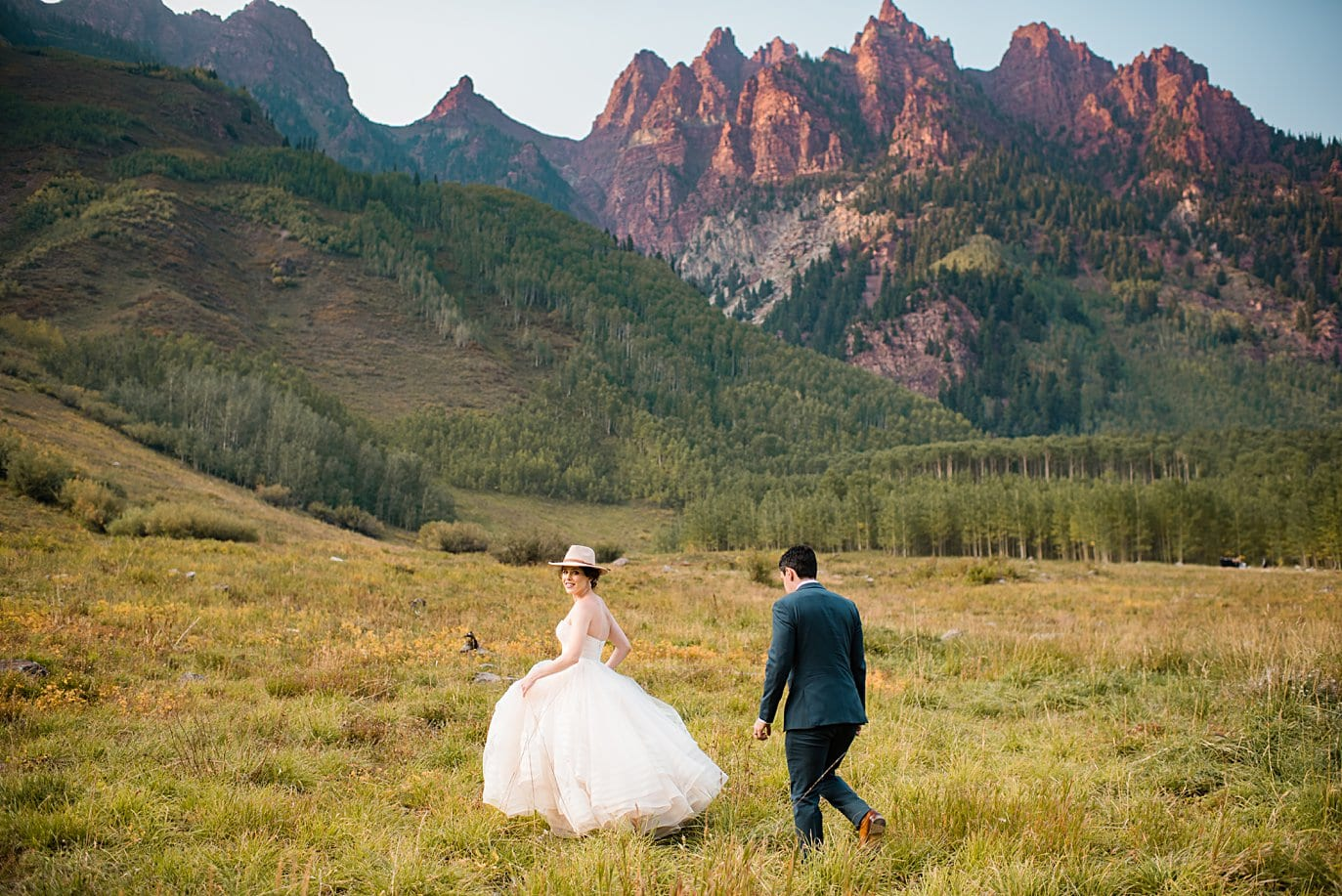 bride in pink hat walks in front of red rocks at fall Maroon Bells wedding by Snowmass wedding photographer Jennie Crate