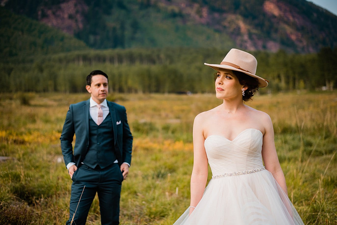 bride with pink hat and groom in navy suite at fall Maroon Bells wedding by Snowmass wedding photographer Jennie Crate