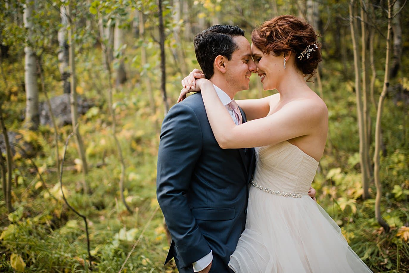 bride and groom cuddle in the early fall aspen trees at fall Maroon Bells wedding by Snowmass wedding photographer Jennie Crate