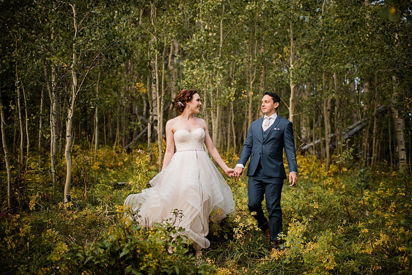 bride and groom walk in aspen trees and fall foliage at fall Maroon Bells wedding by Snowmass wedding photographer Jennie Crate