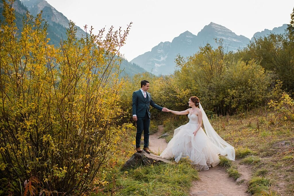 groom helps bride up on rock at fall Maroon Bells wedding by Snowmass wedding photographer Jennie Crate