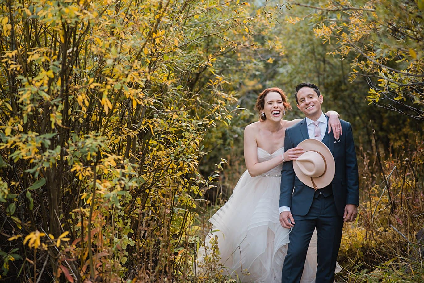 bride with pink hat in fall foliage in Aspen by Denver wedding photographer Jennie Crate