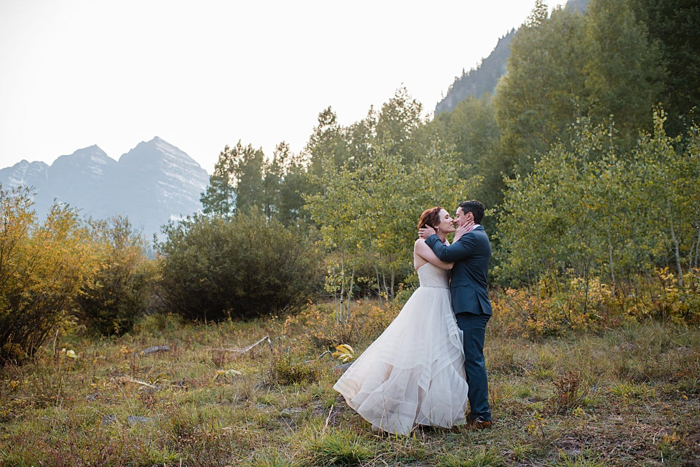 bride and groom kiss in front of Maroon Bells peaks in Aspen by Denver wedding photographer Jennie Crate