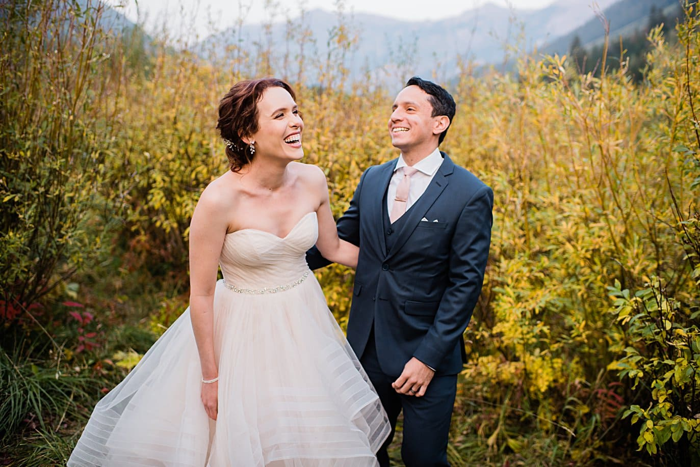 bride and groom laugh during fall wedding session in Aspen by Denver wedding photographer Jennie Crate