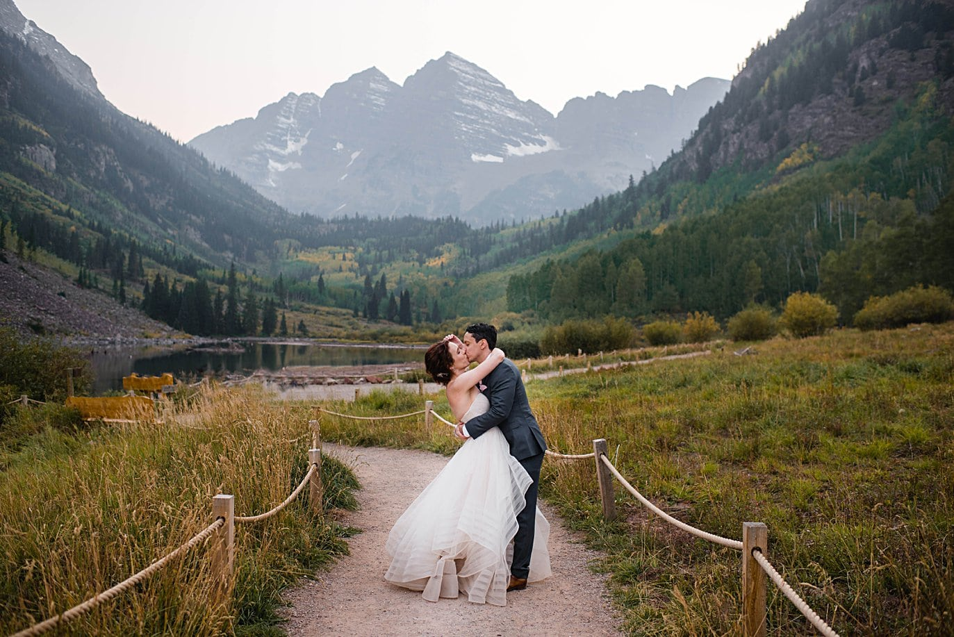 bride and groom kiss on path at Maroon Lake in fall wedding in Aspen by Denver wedding photographer Jennie Crate