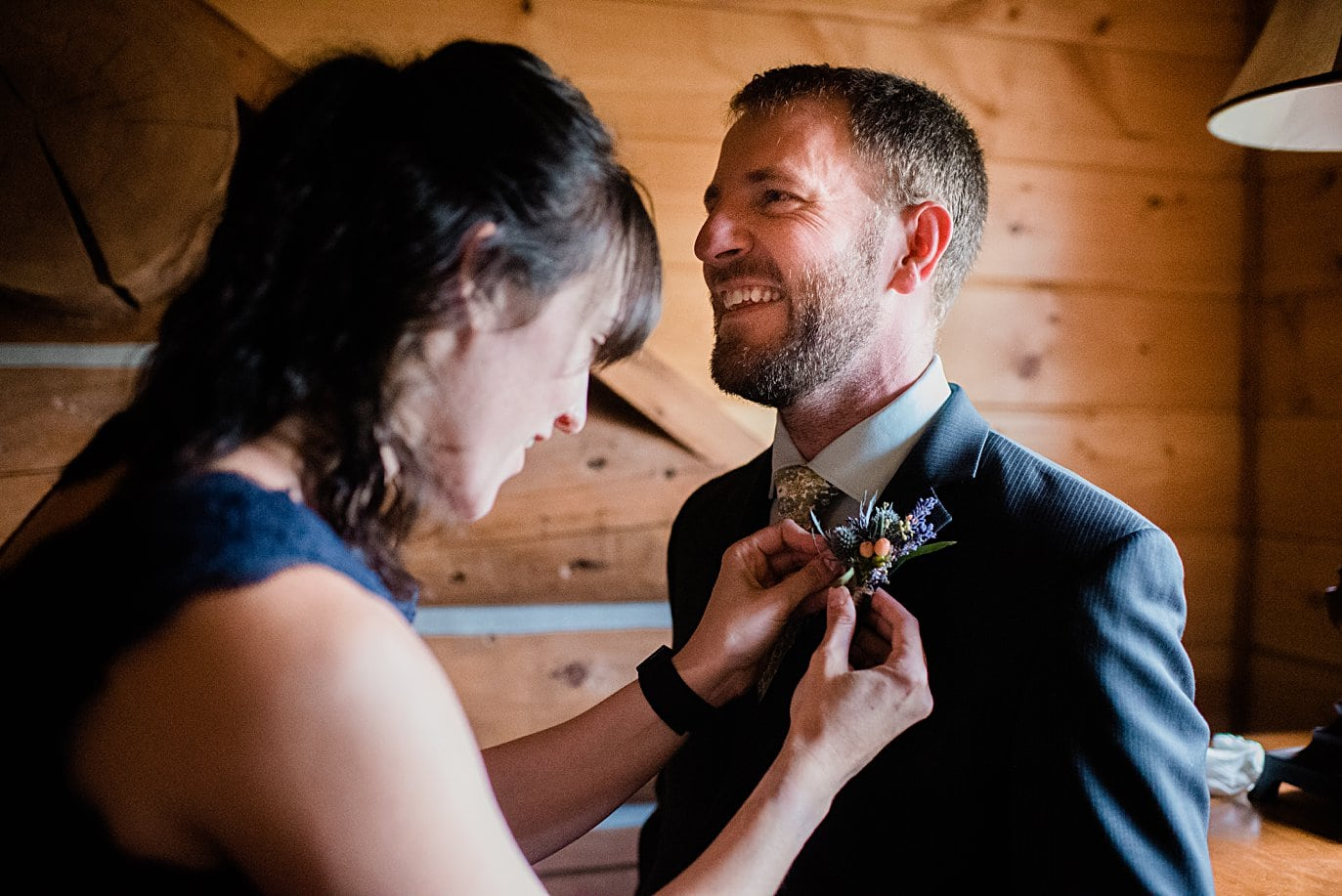 groom getting boutonniere pined on before wedding ceremony at intimate Grand Lake wedding by Grand Lake wedding photographer Jennie Crate
