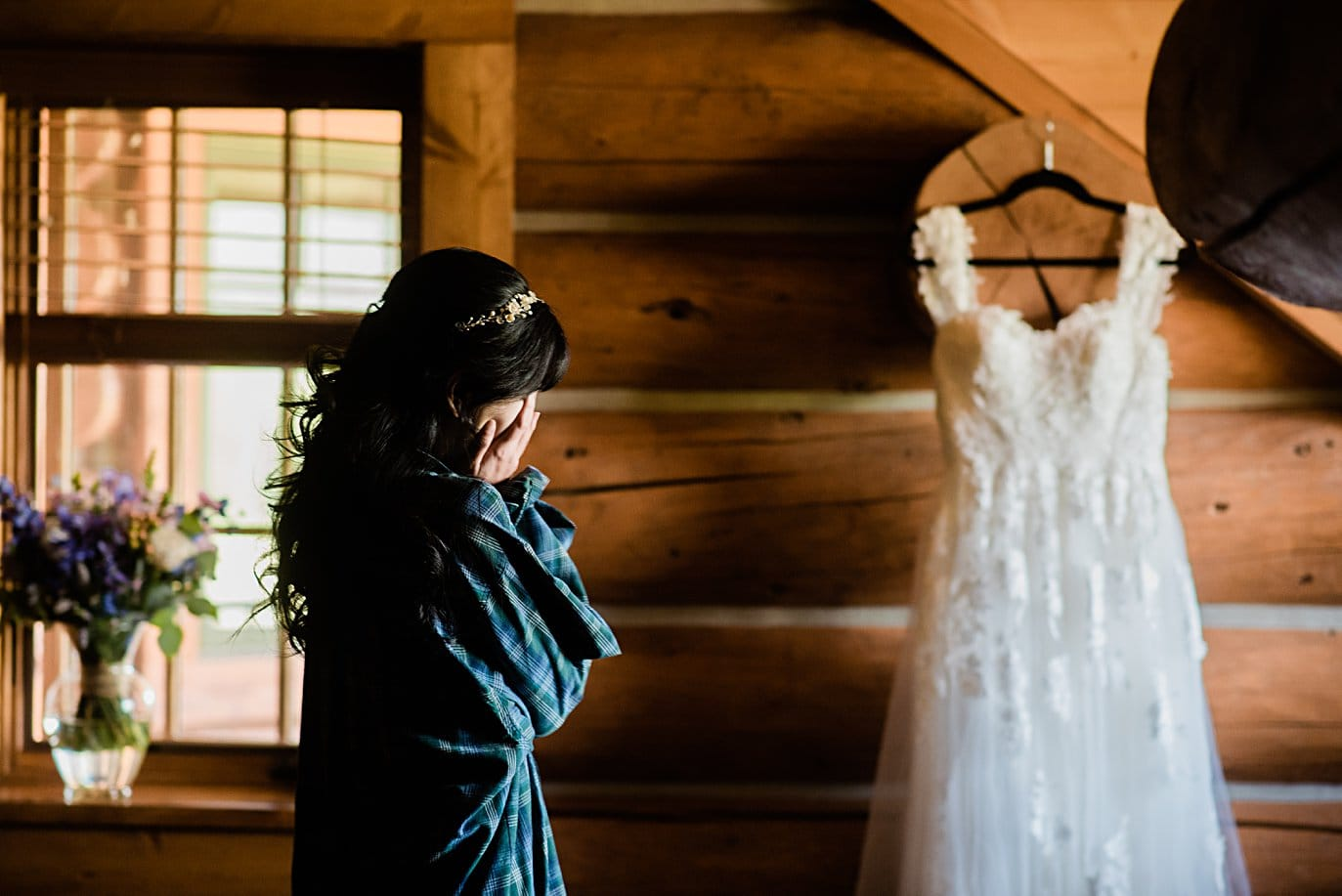 bride overwhelmed with emotion as she looks at wedding dress on wedding day at intimate Grand Lake wedding by Grand Lake wedding photographer Jennie Crate