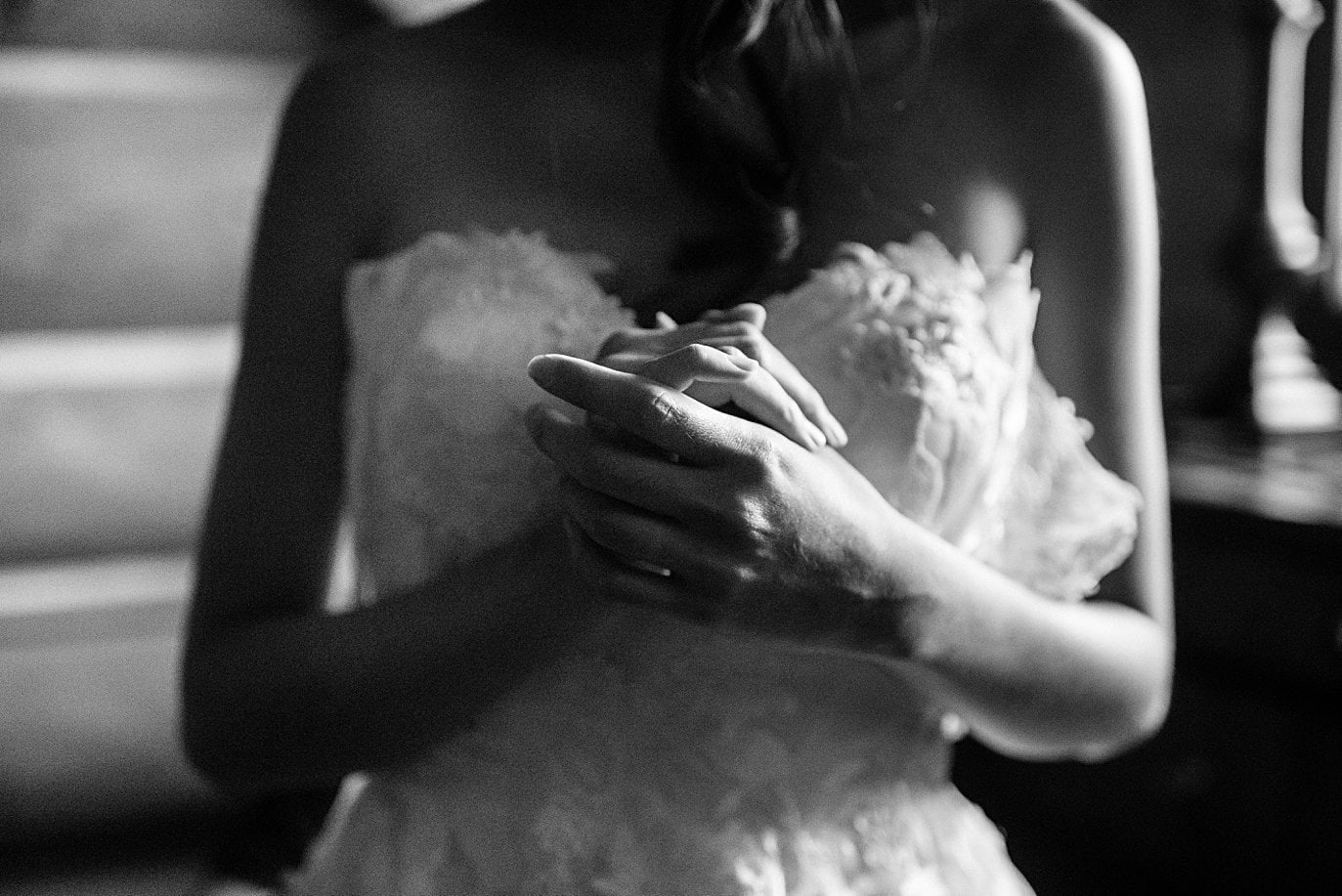 bride clutches hands as she gets laced into wedding dresses at intimate Grand Lake wedding by Grand Lake wedding photographer Jennie Crate