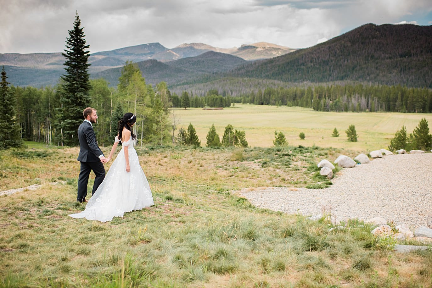 bride and groom walk hand in hand to ceremony at intimate Grand Lake wedding by Grand Lake wedding photographer Jennie Crate