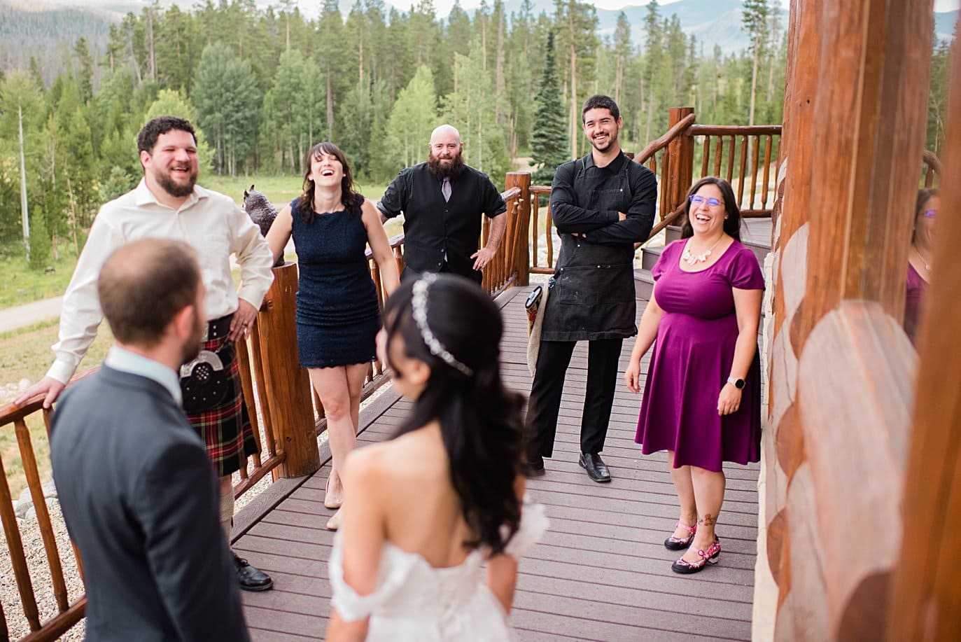 bride and groom talk with friends on porch before ceremony at intimate Grand Lake wedding by Denver wedding photographer Jennie Crate