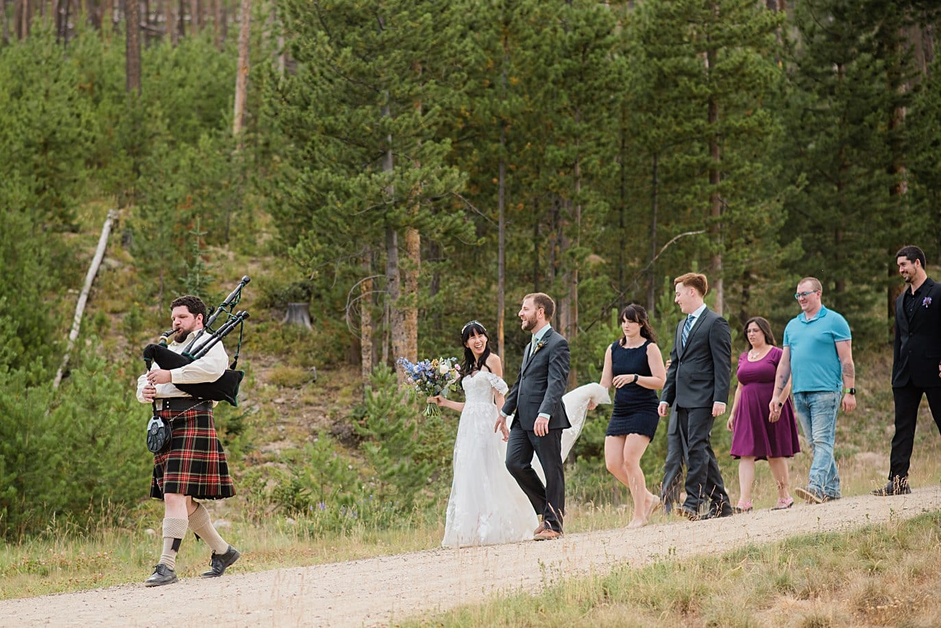 bride and groom walk with friends to wedding ceremony with bagpiper leading the way at intimate Grand Lake wedding by Denver wedding photographer Jennie Crate