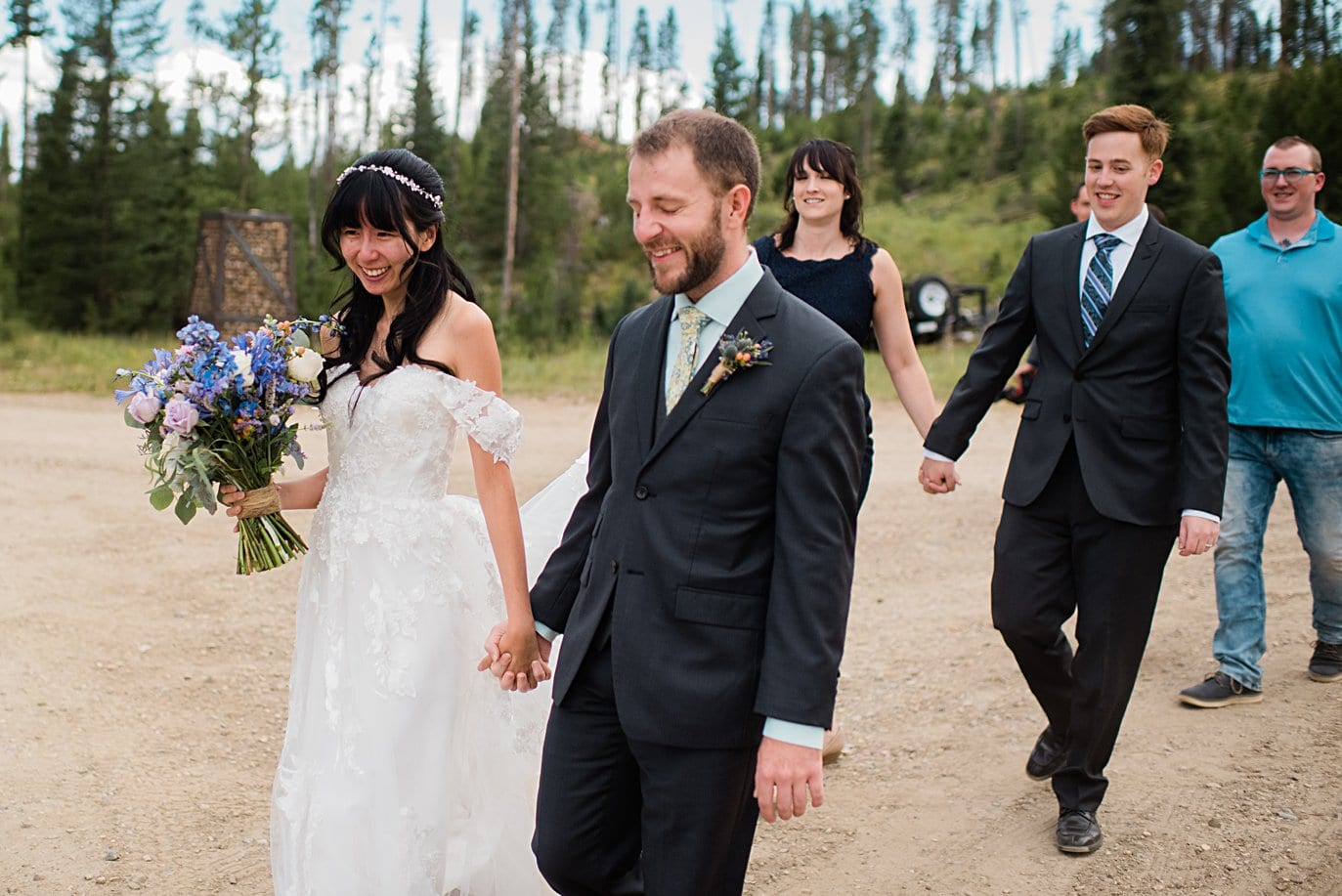 bride and groom walk hand in hand to ceremony in meadow at intimate Grand Lake wedding by Denver wedding photographer Jennie Crate