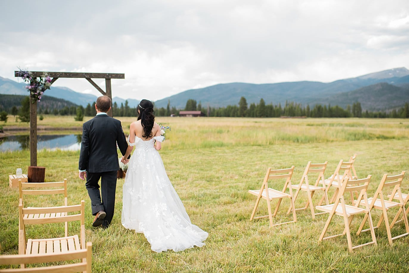 bride and groom approach ceremony at intimate Grand Lake wedding by Denver wedding photographer Jennie Crate