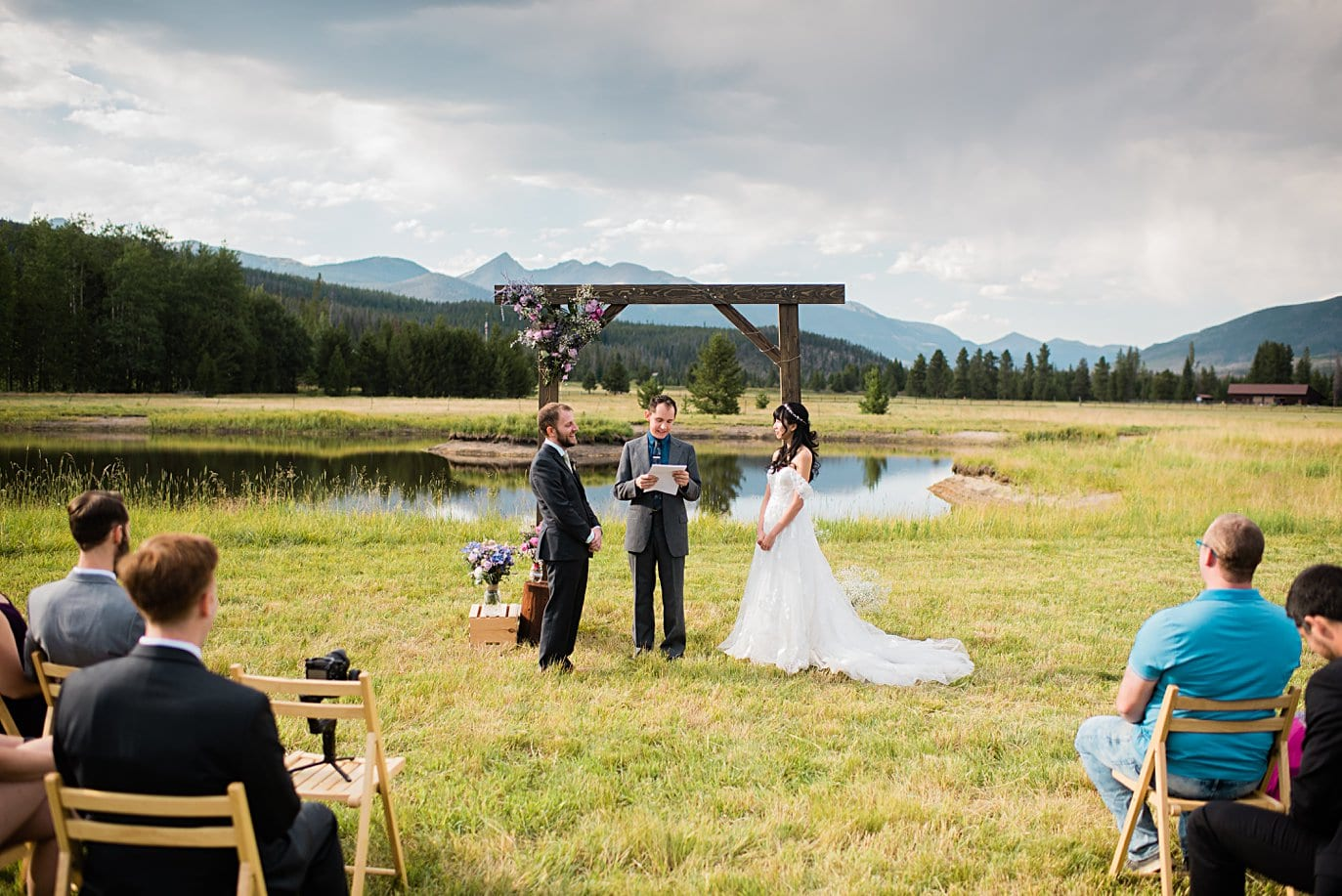 wedding ceremony in meadow with Colorado Mountain view at intimate Grand Lake wedding by Denver wedding photographer Jennie Crate