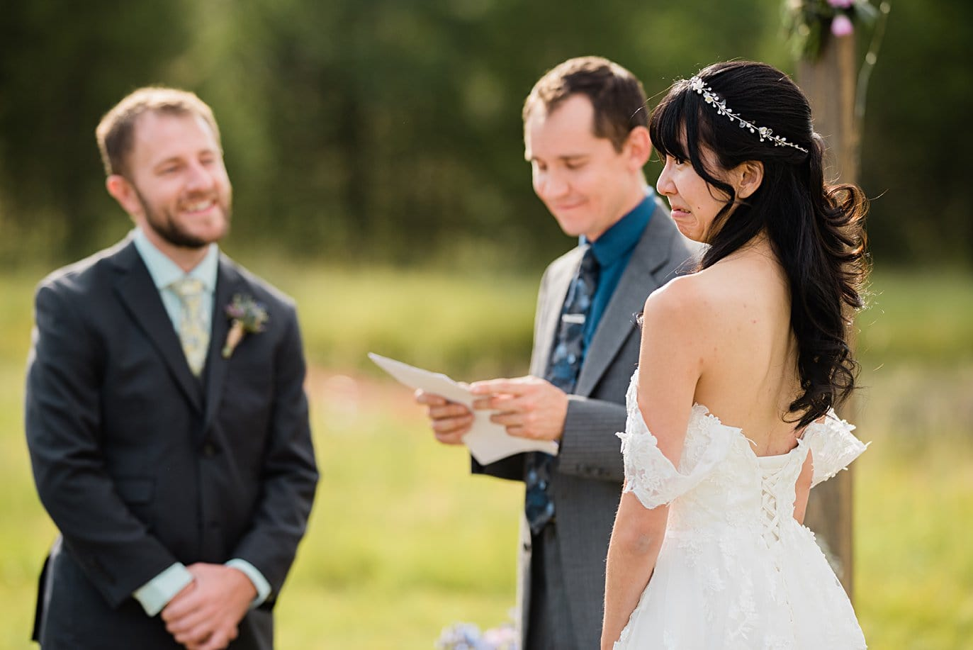 bride and groom share jokes during wedding ceremony at intimate Grand Lake wedding by Denver wedding photographer Jennie Crate